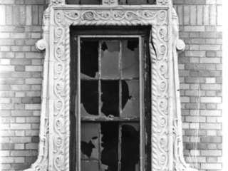 carved window frame around broken glass on Granada Towers