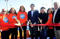 Billy Crystal cutting ribbon for basketball courts