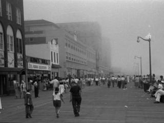 crowded boardwalk on misty day, 1950s